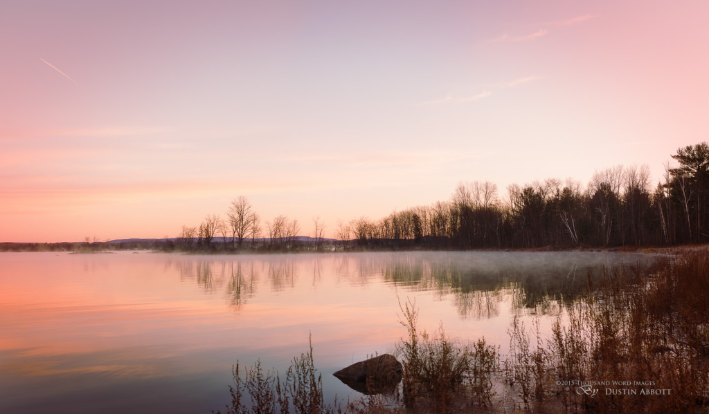 "© 2015 Thousand Word Images by Dustin Abbott It was a frosty sunrise this morning. The day broke crisp and cold, with the temperature hovering around -7C/20F, but I saw the development of beautiful light. Mist rose off the water that is still a lot warmer than the air, and the color was dazzling. It was until I shot my fill that I began to notice the cold at all. This is a four shot panorama combining four vertical frames. I like to shoot vertical frames for a panorama because you end up with a more natural framing after combining, although I also shot a horizontal pano that looks pretty sweet as well. I've always loved this wedge of trees out on the penninsula - it reminds me of a ship sailing off towards the horizon. Technical Information: Canon EOS M3, Canon EF 40mm f/2.8 STM, Processed in Adobe Lightroom CC, Photoshop CC, and Alien Skin Exposure X (use code ""dustinabbott"" to get 10% off) Want to know more about me or make contact? Take a look at my website and find a lot of ways to connect and view my work."