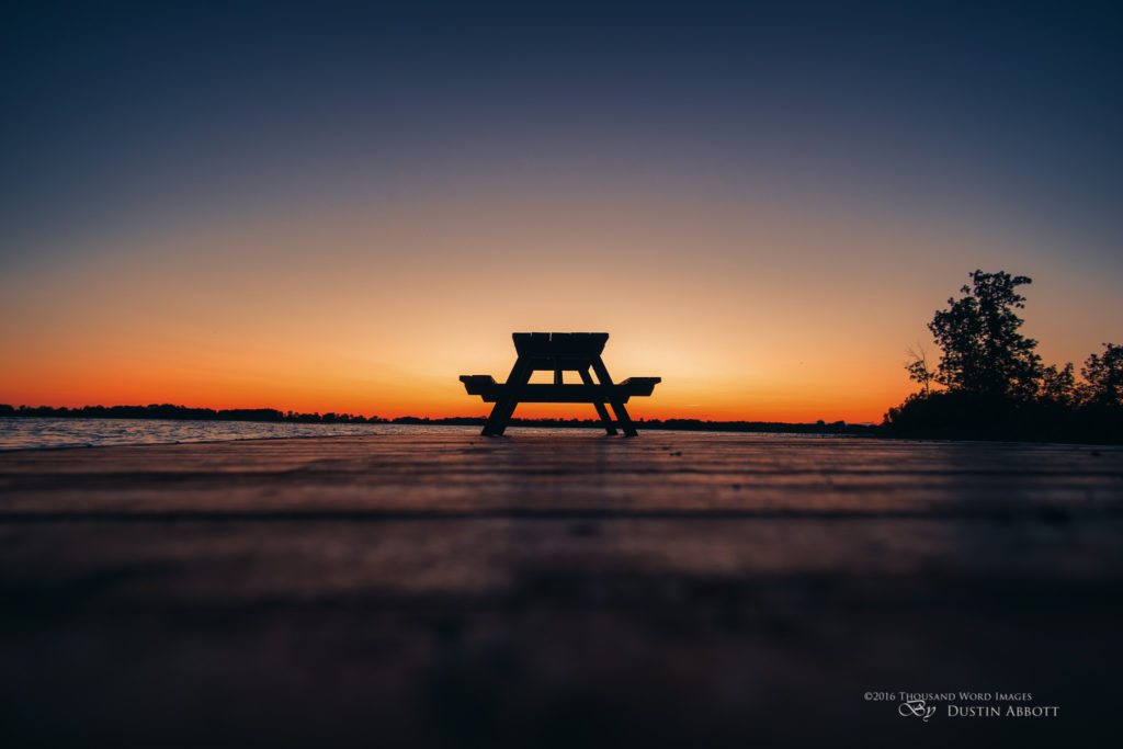 """© 2016 Thousand Word Images by Dustin Abbott  Summer in Ontario, Canada means cottage season for many people.  Those long evenings by the river or the lake enjoying Canadian nature at its finest.  The hardship of winter is a distant memory and we get to complain about the heat instead of the cold.  I shot this image shortly after 9:00 in the evening.  The sun has already dipped below the horizon, but the warm glow lingers.  I silhouetted a picnic table out on a dock.  I kicked the rule of thirds out the door and centered the subject.  The reflected light off the deck boards provided a nice lead in to the picnic table, which silhouetted here takes on almost the appearance of a shrine - which may be appropriate as outdoor pursuits IS the religion for many Canadians.  My work is cut out for me!  Technical Information:  Canon EOS M3 + Rokinon 12mm f/2 NCS,  Processed in Adobe Lightroom CC, Photoshop CC, and Alien Skin Exposure X  (use code """"dustinabbott"""" to get 10% off)   Want to know more about me or make contact?  Take a look at my website and find a lot of ways t"""